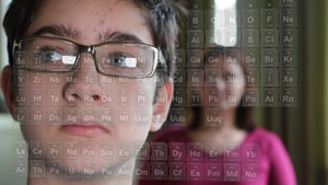 Boy with glasses examines the periodic table